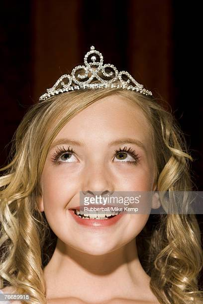 Close-up of girl with tiara looking up smiling
