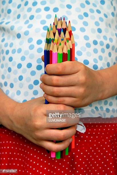close-up of girl's hands holding many colored pencils