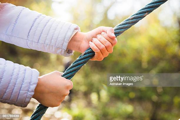 Close-up of girls hands holding rope in forest