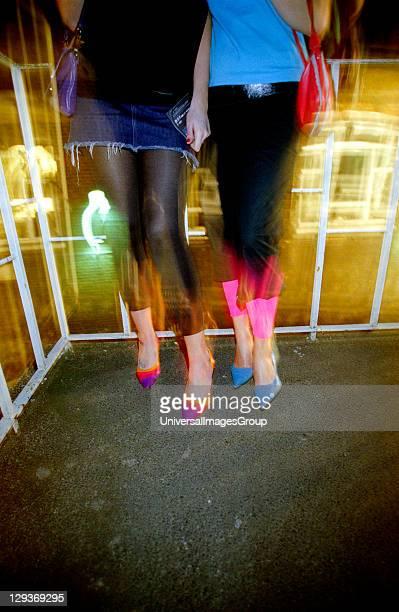 Closeup of girls legs wearing a mini skirt leggings and stileto shoes at 93 Feet East London 2004