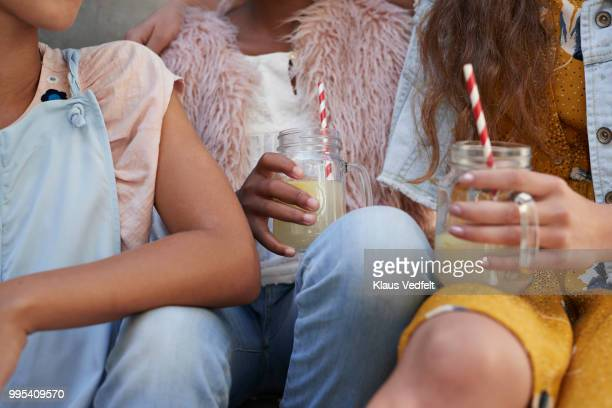 Close-up of girls sitting on staircase & drinking lemonade