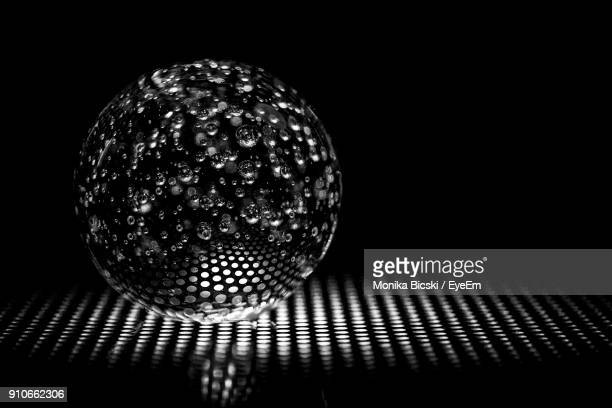 close-up of glass ball on metal grate against black background - metal grate ストックフォトと画像