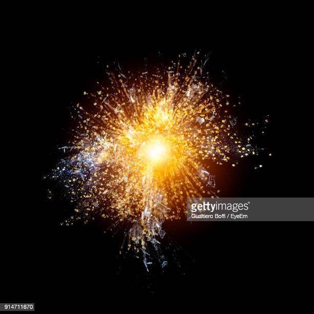 close-up of glass breaking against black background - particle stock photos and pictures