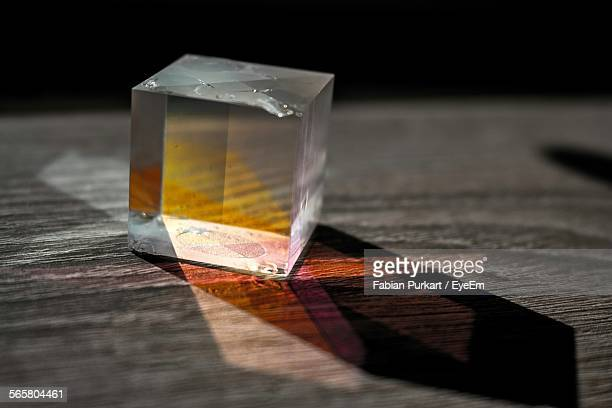Close-Up Of Glass Cube On Wooden Table
