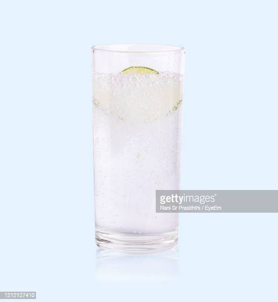 close-up of glass of water against white background - lemon soda stock pictures, royalty-free photos & images
