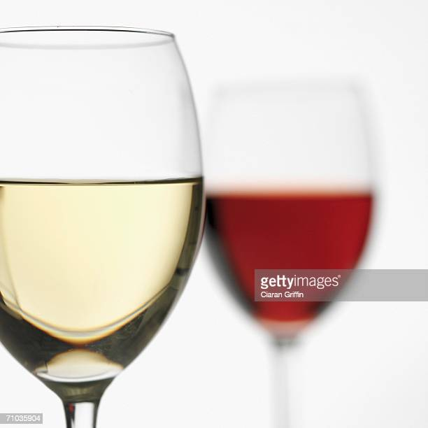 Close-up of glass of white wine with glass of red wine in the background