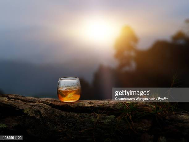 close-up of glass on rock against sky during sunset - bourbon whiskey stock pictures, royalty-free photos & images