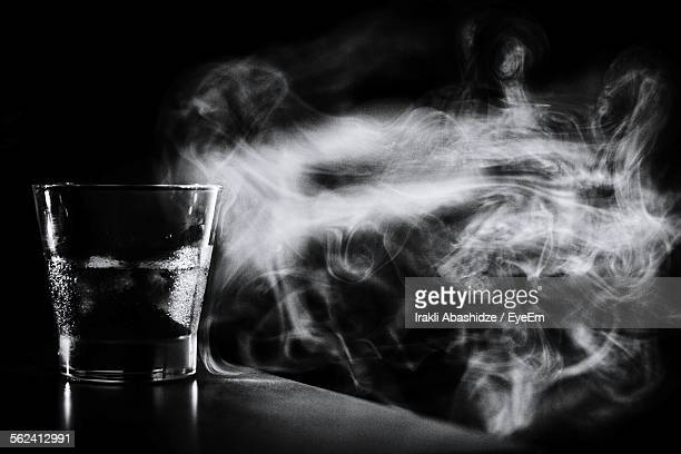 Close-Up Of Glass On Table By Smoke