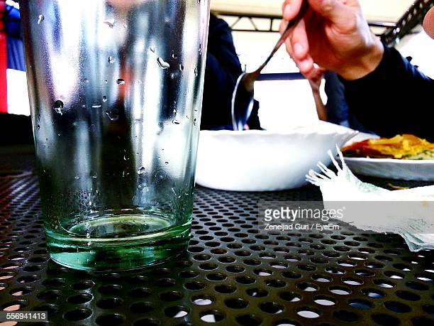Close-Up Of Glass On Table With Person Having Food In Background At Restaurant