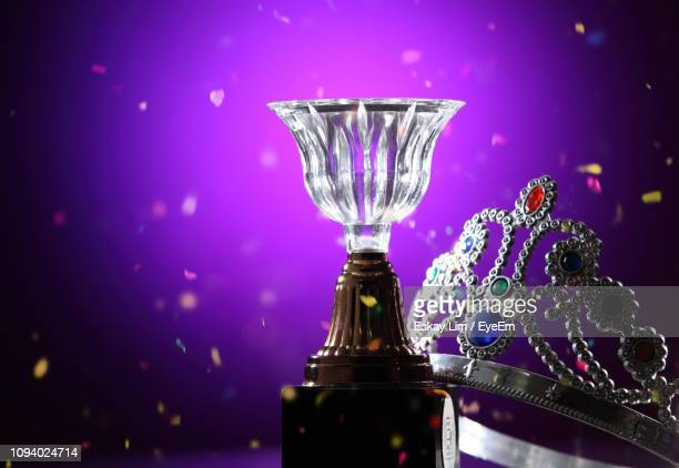 close-up of glass trophy and crown against purple background - crown close up stock pictures, royalty-free photos & images