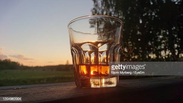 close-up of  glass with vhiskey  on table during sunset - bourbon whiskey stock pictures, royalty-free photos & images