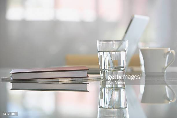 Close-up of glass with water on desk with laptop