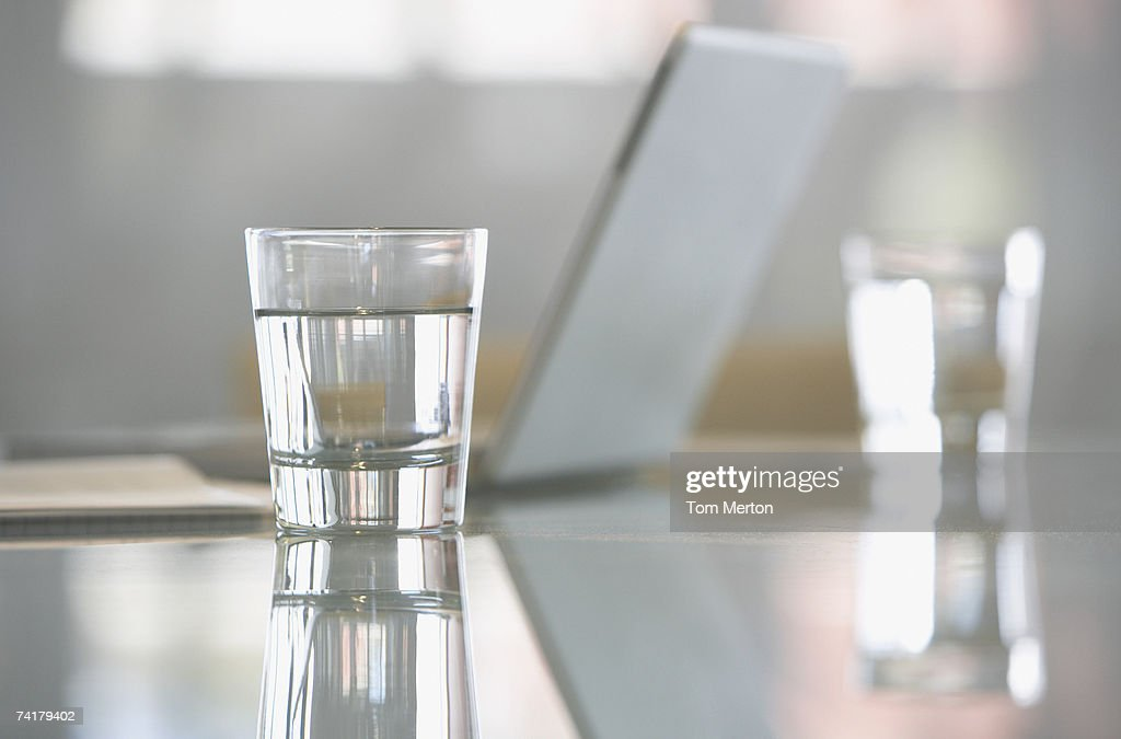 Close-up of glass with water on desk with laptop : Stock Photo