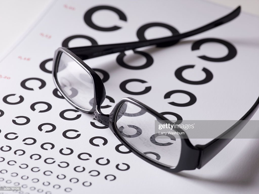 Close-up of glasses on eye exam chart : Stock Photo