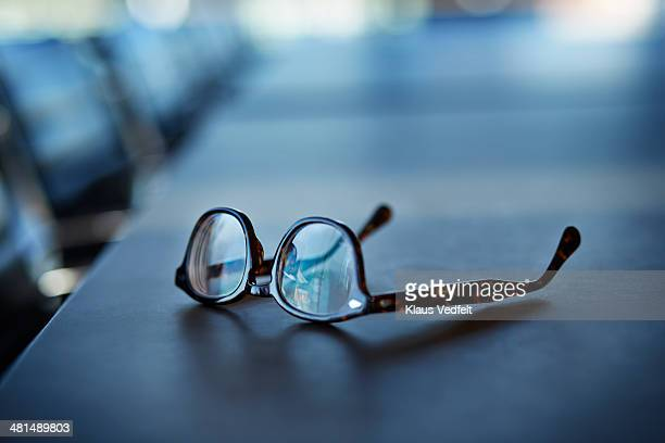 close-up of glasses on table - brille stock-fotos und bilder
