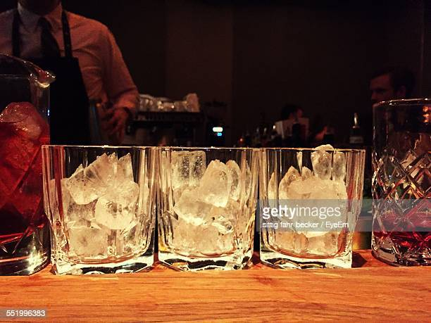 Close-Up Of Glasses With Ice Cubes On Table In Bar