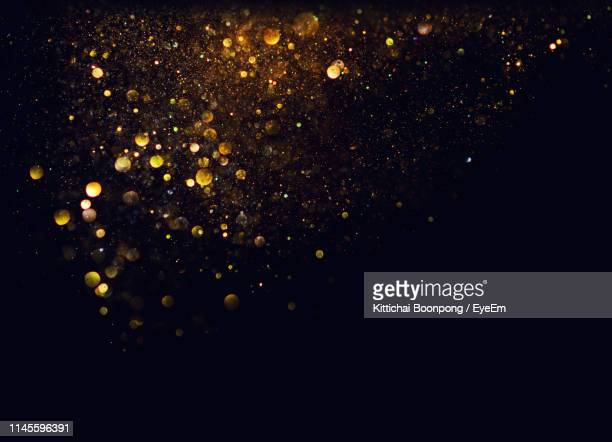 close-up of glitter against black background - gold coloured stock pictures, royalty-free photos & images