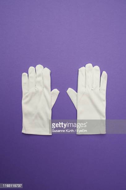 close-up of gloves on purple background - purple glove stock pictures, royalty-free photos & images