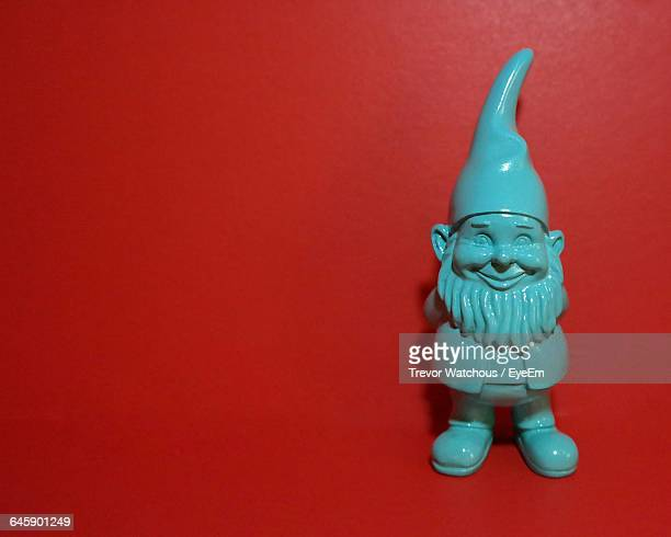 close-up of gnome over red background - garden gnome stock photos and pictures