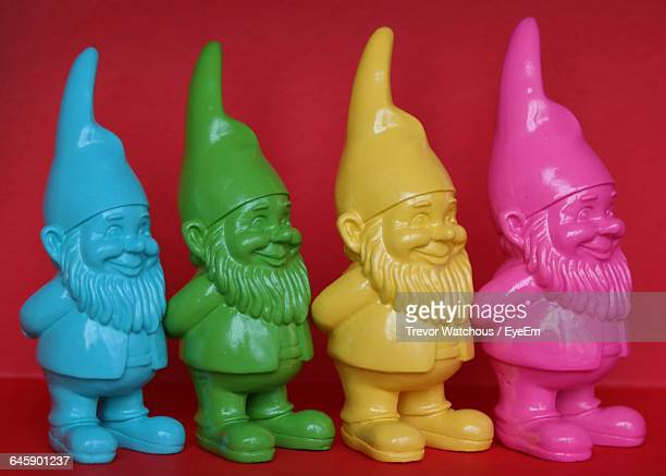Close-Up Of Gnomes Over Red Background