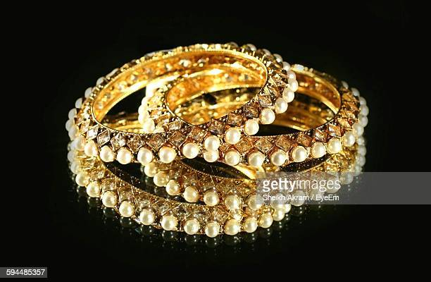 Close-Up Of Gold Bangles On Black Background