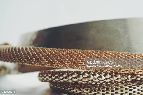 Close-Up Of Gold Bangles On Table