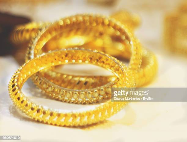 close-up of gold bangles on table - bangle stock pictures, royalty-free photos & images