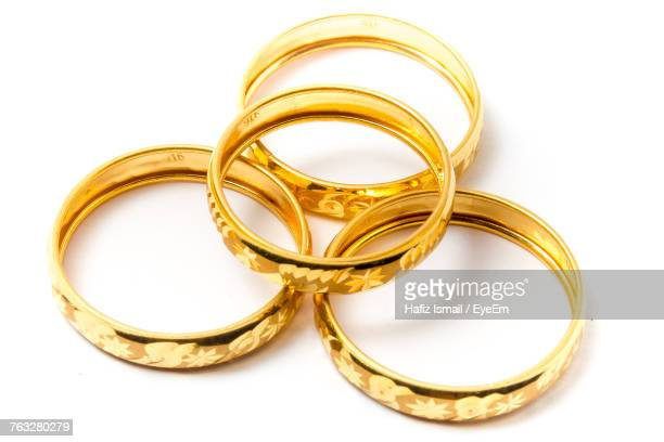 close-up of gold bangles over white background - バングル ストックフォトと画像