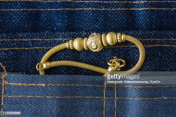 close-up of gold bracelet in jeans pocket - brazalete pulsera fotografías e imágenes de stock