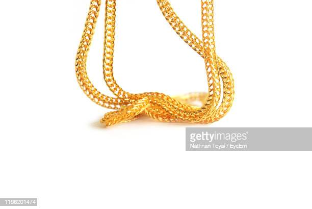 close-up of gold chain against white background - gold chain necklace stock pictures, royalty-free photos & images