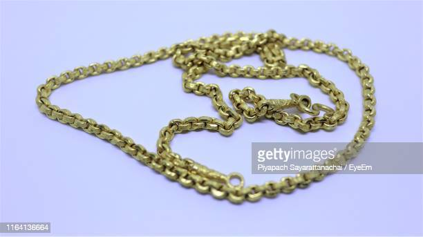 close-up of gold chain necklace on white background - gold chain necklace stock pictures, royalty-free photos & images