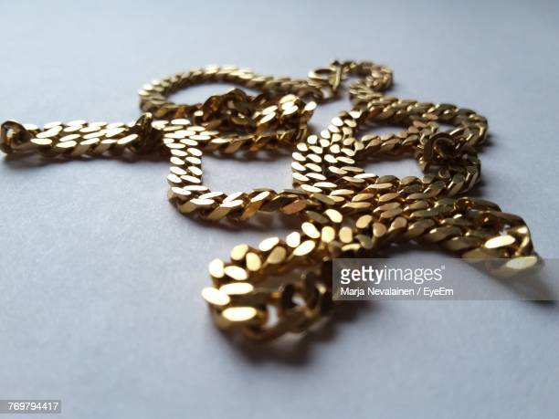close-up of gold chain on white background - choker stock photos and pictures