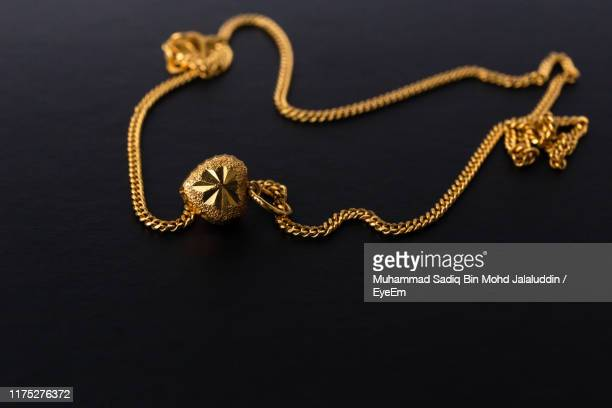 close-up of gold chain over black background - gold chain necklace stock pictures, royalty-free photos & images