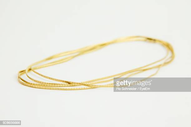 Close-Up Of Gold Chain Over White Background