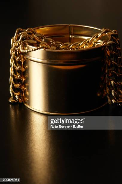 close-up of gold chains in container on table - 金のネックレス ストックフォトと画像