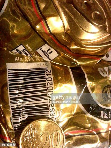 Close-Up Of Gold Coin On Crushed Beer Can