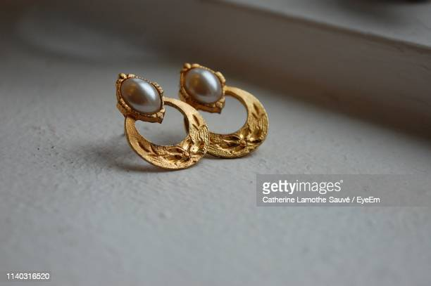 close-up of gold earrings on table - earring stock pictures, royalty-free photos & images