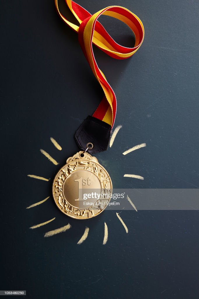 Close-Up Of Gold Medal Against Black Background : Stock Photo