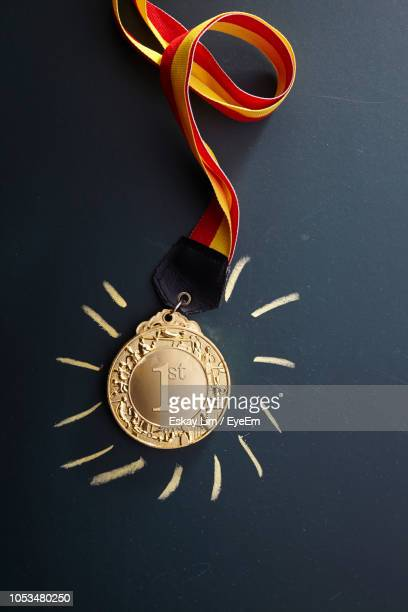 close-up of gold medal against black background - gold medal stock pictures, royalty-free photos & images