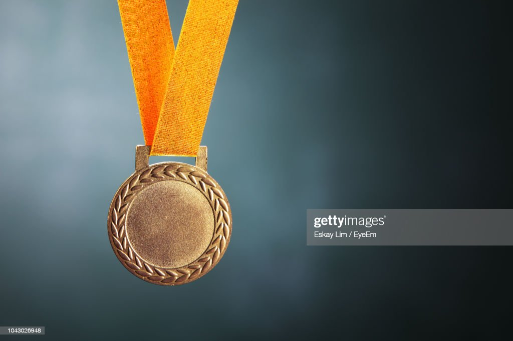 Close-Up Of Gold Medal Against Blackboard : Stock Photo