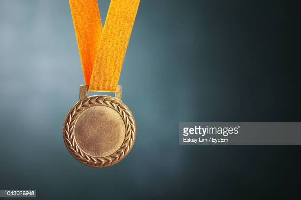 close-up of gold medal against blackboard - winnen stockfoto's en -beelden