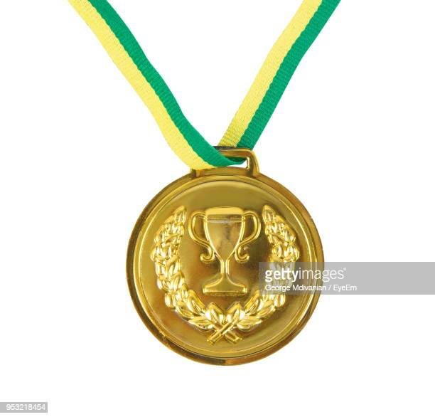 Close-Up Of Gold Medal Against White Background