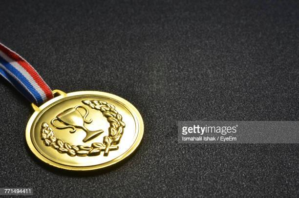 close-up of gold medal on black table - メダル ストックフォトと画像