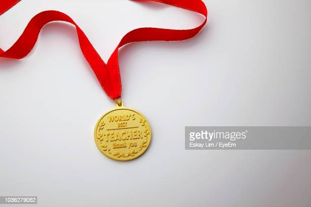 Close-Up Of Gold Medal Over White Background