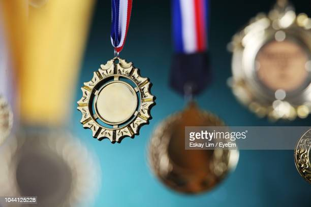 Close-Up Of Gold Medals Against Blackboard