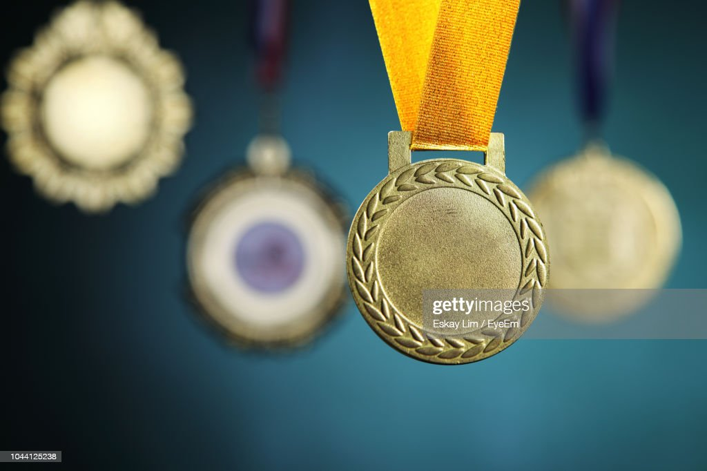 Close-Up Of Gold Medals Hanging Against Blackboard : Stock-Foto
