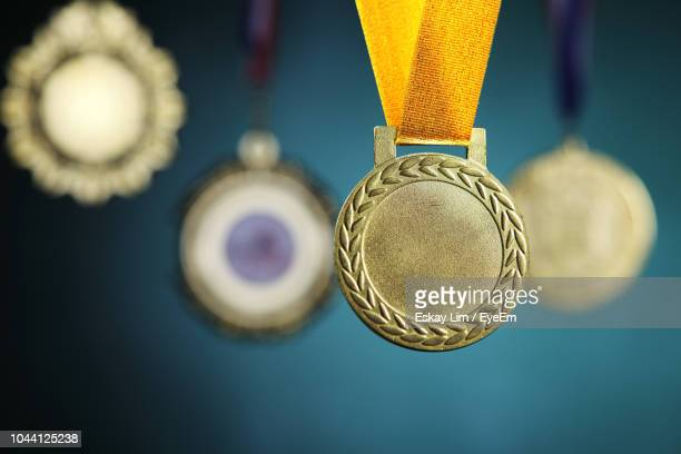 Close-Up Of Gold Medals Hanging Against Blackboard