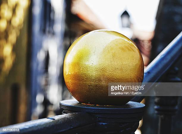 Close-Up Of Gold Metallic Sphere On Railing