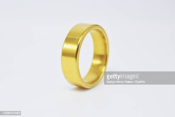 close-up of gold ring against white background - white gold stock pictures, royalty-free photos & images