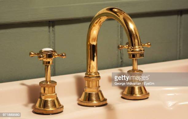 close-up of gold tap and faucet on sink - 家庭の備品 ストックフォトと画像